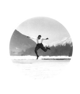 La imagen muestra una fotografía circular en la que en el medio justo podemos ver a un joven patinador en el aire, en plena pirueta. A su alrededor el paisaje de un lado helado y al fondo las montañas nevadas. Pulse para ampliar.
