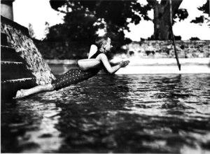 La imagen muestra a un niño con bañador de cuerpo entero y una especie de boya atada a la espalda en el momento de zambullirse en una piscina. Tiene todo el cuerpo estirado, los brazos flexionados y las manos juntas para sumergirse. Pulse para ampliar.