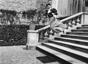 La imagen muestra parte de las escaleras de piedra que parecen dar acceso a una gran casa. Sobre la balaustrada está la figura de una mujer joven que se está deslizando pasamanos abajo con cara de diversión y la falda ondeando. Pulse para ampliar.