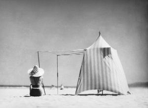 La imagen muestra a una mujer sentada de espaldas al espectador sobre la arena de la playa. A su lado una especie de tienda de campaña de tela a rayas cuyas paredes están hinchadas por el viento que sopla. Pulse para ampliar.