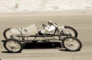 La imagen muestra una fotografía tomada en picado, es decir, desde arriba, en la que se ve un coche de carreras pilotado por un hombre, en plena competición. Las líneas borrosas del paisaje del fondo y de los radios de las ruedas del coche nos indican que va a bastante velocidad. Pulse para ampliar.