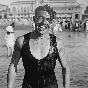 La imagen muestra una fotografía de un hombre joven recién salido del mar. Está vestido con un bañador de cuerpo entero y por su cabeza y su pecho caen chorros de agua. Tiene la cabeza inclinada y sonríe abiertamente a la cámara. Pulse para ampliar.