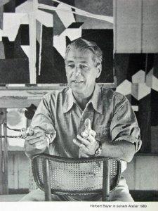 Herbert Bayer - Retrato fotográfico en su estudio (1960) La imagen es una fotografía en la que aparece Bayer sentado en una silla en su estudio. Tras él pueden verse algunos cuadros suyos.Pulse para ampliar.