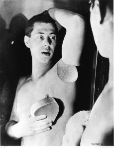 Herbert Bayer - Autorretrato. Fotomontaje (1932) En la imagen aparece el propio Bayer delante de un espejo: es un plano medio (cortado a la altura de la cintura) y aparece con el torso desnudo, casi de perfil, con el brazo izquierdo levantado por encima de la cabeza pero separado del hombro. El brazo derecho aparece pegado al torso y con la mano derecha sostiene una rodaja que entendemos que es la parte del brazo izquierdo que falta. Bayer mira su brazo cortado con gesto de sorpresa. Pulse para ampliar.