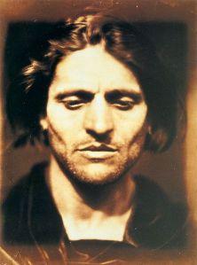 Julia Margaret Cameron - Iago: Estudio de un italiano (1867) La fotografía muestra el primer plano de un hombre joven, de frente, con el cabello oscuro y largo y barba incipiente. Dirige su mirada hacia abajo, dándole aspecto meditabundo. Pulse para ampliar.