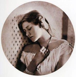 Julia Margaret Cameron - Tristeza (1864) La fotografía muestra un plano medio de una muchacha joven, de tres cuartos apoyada sobre una celosía, mirando hacia la izquierda, con la cabeza ligeramente inclinada hacia abajo y los ojos semicerrados. Su mano derecha acaricia un colgante que lleva al cuello.