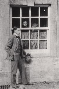 Fotografía de William Nicholson y James Pryde (1908) En la fotografía aparece Nicholson en el exterior de una casa, apoyado en una ventana. Al otro lado de la ventana, en el interior de la casa, se adivina a James Pryde, que sostiene un niño en brazos.