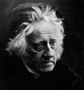 Julia Margaret Cameron - Retrato de Sir John Herschel con gorro (1864) La fotografía muestra un primer plano de un hombre mayor, de pelo cano y alborotado, que cubre su cabeza con una especia de boina, que apenas se aprecia. Su rostro está ligeramente vuelto hacia la derecha y su mirada se dirige hacia abajo.