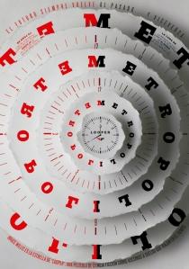 """Portada de La Luna de Metrópoli (Diario El Mundo) Octubre de 2012 - La imagen muestra una serie de cñirculos de papel superpuestos en tamaño decreciente como si fueran esferas de un reloj. En cada uno de ellos aparece en la parte izquierda la palabra """"Metrópoli"""" en rojo y escrita al revés y en la parte derecha la misma palabra escrita en negro y en sentido correcto. El tema de la portada es la película """"Looper"""" cuyo argumento trata de viajes hacia adelante y hacia atrás en el tiempo. Pulse para ampliar."""