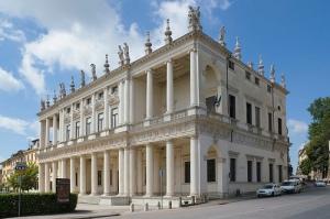 Andrea Palladio - Palazzo Chiericati (1550) - Vicenza - La imagen muestra el exterior, desde una esquina, del palacio. Tiene dos alturas y cada piso está adornado con columnas que forman pórticos en el frente, mientras que en el lateral, cuyo muro es macizo, se aprecia que, en realidad, hay tres pisos, que quedan disimulados en el frente por la doble columnata superpuesta. Pulse para ampliar.