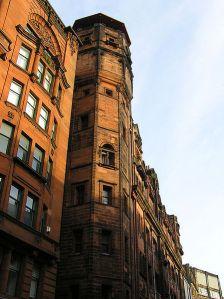 """Charles Rennie Mackintosh - Fachada del edificio del Glasgow Herald (1894) - la imagen muestra la fachada de la sede del periodico Glasgow Herald, de unas seis plantas de altura y, más concretamente, uno de los extremos de esa fachada que aparece rematada en forma de torre poligonal en toda su longitud (lo que hace que al edificio se le conozca como """"El faro""""). Pulse para ampliar."""