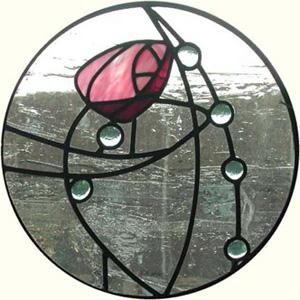 Charles Rennie Mackintosh - Diseño de vidriera - la imagen muestra una vidriera de forma circular dividida por una serie de lineas curvas. en la parte superior aparece el capullo de una rosa y, salpicados a los largo de una de las líneas, aparecen una serie de círculos de menos tamaño que asemejan gotas de rocío. Pulse para ampliar.