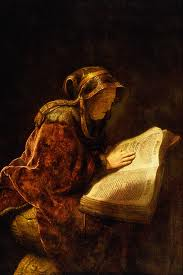 - La imagen muestra un cuadro en el que aparece una mujer anciana, de cuerpo entero, sentada e inclinada sobre un gran libro abierto por la mitad. Va vestida con ropas amplias y lleva la cabez cubierta con una especie de paño. El fondo del cuadro es muy oscuro y la luz, en tonos dorados, ilumina el libro abierto y la mano que la anciana tiene sobre él y, de algún modo, refleja la luz y posibilita que veamos los rasgos de la mujer. Pulse para ampliar.