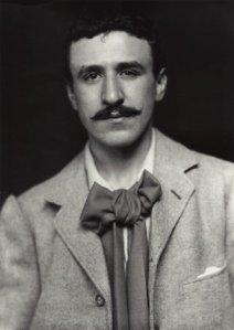 Charles Rennie Mackintosh - Retrato (c. 1893) - la imagen muestra un plano medio de un hombre joven, que mira de frente al espectador, moreno y con bigote. Vestido con una chaqueta de color claro, camisa blanca y corbata de lazo de gran tamaño. Pulse para ampliar.