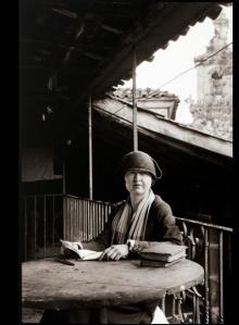 Alfred Anderson - Retrato de Ruth M. Anderson en Galicia (1926) la imagen muestra a Ruth sentada a una mesa en una especie de balcón. Al fondo se aprecia una construcción de piedra (probablemente la torre de una iglesia). Está revisando unas notas y mira a la cámara. A pesar de que lleva sombrero, se puede apreciar su rostro redondo y rubicundo, sus ojos claros y la sonrisa que esboza. Pulse para ampliar.