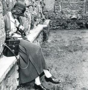 Alfred Anderson - Ruth M. Anderson cargando la cámara estereoscópica en Pontevedra (1925) - La fotografía muestra a Ruth sentada en un banco de piedra pegado a un muro, vestida con un traje de chaqueta y con un sombrero, cargando la cámara con un carrete. Tiene la cabeza baja y está como absorta en la operación. Pulse para ampliar.
