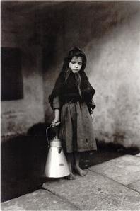 Ruth M. Anderson - La pequeña lechera de Noia (1924) - La fotografía muestra una niña de unos cinco años, vestida muy pobremente y descalza que lleva en su mano derecha una sella o recipiente de metal para acarrear leche. Pulse para ampliar.