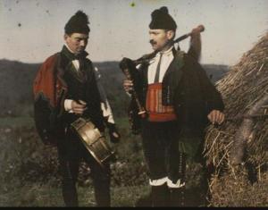 Ruth M. Anderson - Gaiteiros (1925) La fotografía muestra dos hombres vestidos con el traje típico gallego: calzon, polainas y botas, camisa, refajo y chaqueta y gorro de dos picos con borlas. Uno de ellos lleva un pequeño tambor y otro una gaita. Pulse para ampliar.