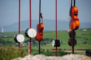 Pierre Sauvageot - Champs harmoniques (Distrito de los Lagos - Inglaterra, 2012) - La imagen muestra una instalación con una serie de postes donde están atados varios instrumentos de percusión (tambores) y cuerda (violonchelos) en medio de un paisaje elevado. Pulse para ampliar.