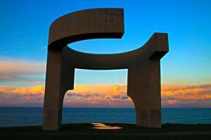 Eduardo Chillida - Elogio del Horizonte (1990) - La imagen muestra una estructura de gran tamaño, realizada en hormigón y de forma semicircular, que se asemeja a una especie de ventana gigante sobre el mar. Pulse para ampliar.