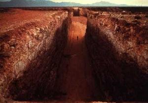 Michael Heizer - Double Negative (1970) - La imagen muestra la vista del interior de una de las zanjas en donde se aprecia, en tamaño muy pequeño, la figura de una persona. Al fondo, al otro lado de un barranco, puede observarse el comienzo de la segunda zanja. Pulse para ampliar.