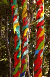 Agustín Ibarrola - Bosque en O Rexo (Allariz - Ourense) - La imagen muestra un plano detalle de tres troncos de árbol totalmente recubiertos con pinturas de colores vivos (rojo, amarillo, negro, verde, azul, naranja). Pulse para ampliar.