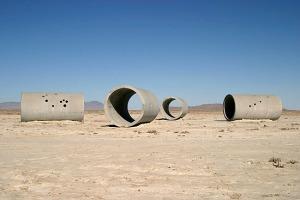 Nancy Holt - Sun Tunnels (Utah) 1973 - La imagen muestra cuatro grandes cilindros situados en un paisaje desértico, dispuestos en forma de cruz. En dos de ellos vemos una serie de agujeros que son los que, al incidir los rayos del sol, proyectan en su interior los dibujos con luz de las constelaciones de Cáncer y Capricornio. Pulse para ampliar.
