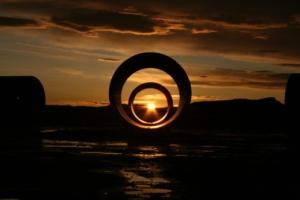 Nancy Holt - Sun Tunnels (Utah) 1973 - La imagen muestra una fotografía tomada en una puesta de sol. Dos de los cilindros están alineados con respecto a la posición del sol, que se aprecia, mientras se va poniendo, en el eje central de los círculos. Pulse para ampliar.