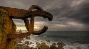 Eduardo Chillida - Peine del Viento (1976) - La imagen muestra una viga de hierro  insertada en la roca de la costa que extiende una serie de brazos (que se asemejan a dedos) en dirección al mar. Pulse para ampliar.