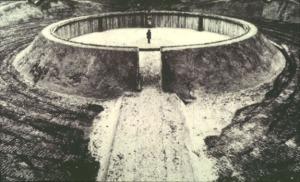 Robert Morris - Observatory (1970-77) - la imagen muestra una construcción circular de unos 10 metros de diámetro, formada por un talud de tierra sostenido por una estructura de madera y metal. En el centro de la construcción se aprecia una figura humana de pequeño tamaño, que nos da una idea de la proporción del conjunto. Pulse para ampliar.