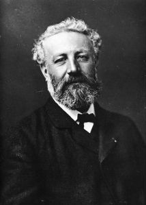 Julio Verne fotografiado por Felix Marie Tournachon (Nadar) en 1878 - La imagen muestra una fotografía en blanco y negro en la que el escritor Julio Verne aparece en un primer plano largo (es decir, cortado un poco más abajo de los hombros), con el pelo y la barba entrecanos y mirada sonriente. Pulse para ampliar.