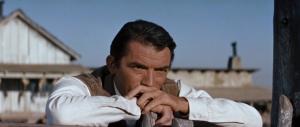 """Gregory Peck en un fotograma de """"Horizontes de grandeza"""" (William Wyler, 1958) - La imagen muestra al protagonista en un plano medio apoyado en una cerca de madera, vestido como un hombre de ciudad (camisa, chaleco, corbata) y con gesto pensativo. Pulse para ampliar."""