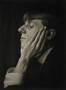 Frederick Evans - Retrato de Vincent Aubrey Beardsley (1894) - La imagen muestra una fotografía en blanco y negro en la que aparece el primer plano de perfil de un muchacho joven, con el pelo de color claro y cortado a la taza. Tiene una nariz ganchuda y prominente y apoya la mejilla en una mano grande y de dedos muy largos y huesudos. Pulse para ampliar.