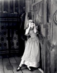 """Lillian Gish en una escena de """"El Viento"""" (Victor Sjöstrom, 1928) - La imagen muestra a una muchacha joven, de apariencia frágil y delicada, apoyada en la puerta de lo que parece una vivienda contruida totalmente en madera con las manos en la cabeza en gesto de desesperación y temor. Pulse para ampliar."""