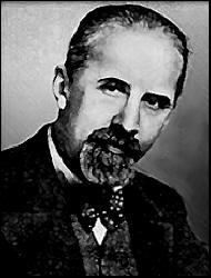 Ivan Bilibin (c. 1930) - La imagen muestra una fotografía de Ivan Bilibin en un primer plano, con la cabeza ligeramente inclinada hacia la derecha y gesto serio. Luce bigote y perilla. Lleva el pelo peinado hacia atrás y va vestido con chaqueta, chaleco y camisa adornada con una pajarita. Pulse para ampliar.