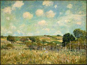 Alfred Sisley - Prado (1875) - La imagen muestra un paisaje de un prado con colinas de relieve suave en último plano y un pequeño grupo de árboles en el lado derecho. Todo está representado en tonos verdes y amarillentos, salvo el cielo, azul salpicado de nubes blancas. Pulse para ampliar.