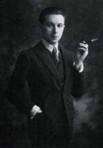 Romain de Tirtoff (Erté) en 1924 - la fotografía muestra un plano medio largo de un joven vestido con traje y corbata, que mira atentamente a la cámara con aire de superioridad y que en su mano izquierda sostiene un cigarrillo al final de una boquilla larga. Pulse para ampliar.l