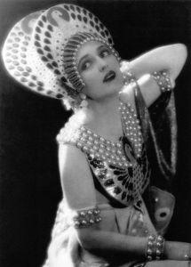 """La actriz Carmel Myers luciendo uno de los diseños de Erté para la película """"Ben-Hur"""" (Fred Niblo, 1925) - La iLa fotografía, en blanco y negro, muestra un plano medio visto desde arriba de una mujer luciendo un complicado tocado de forma ovoide en la cabeza, de color claro y adornado con piedras oscuras. Lleva un vestido sin mangas con cuello formado por varias cuentas de perlas y pectoral metálico adornado también con piedras. Pulse para ampliar."""