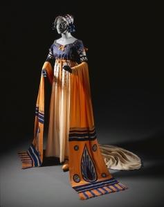 """Romain de Tirtoff (Erté) - Diseño de vestido para la ópera """"Tosca"""" de G. Puccini (1920) - La imagen muestra un maniquí que luce un vestido de talle alto, cuerpo azul violeta y falda naranja. Las mangas caen como si de una capa se tratase y son también naranjas con dibujos geométricos en azul. Pulse para ampliar."""