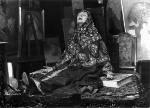 """Maruska posando para """"Mujer en el páramo"""" (1920) - La imagen muestra una fotografía en blanco y negro donde aparece la mujer del pintor, ataviada con las mismas ropas que la mujer del cuadro anterior y con la misma pose. Pulse para ampliar."""