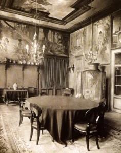 Estancia del castillos de Emmahof con las pinturas restauradas por A.M. Mucha en 1882 - La imagen muestra una fotografía en blanco y negro donde se aprecia el interior de una estancia con una mesa de comedor alargada y sus sillas en primer plano y con los muros y techos decorados con pinturas, que apenas se distinguen. Pulse para ampliar.