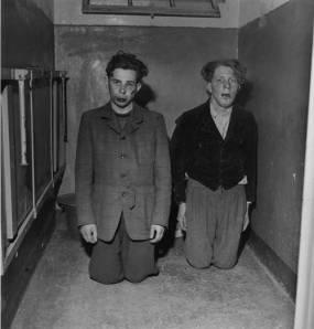 """Lee Miller - """"Guardianes de Buchenwald vestidos de paisano para huir piden clemencia tras ser apaleados"""" (1945) - La imagen muestra a dos hombres muy jóvenes, uno moreno y otro rubio, de rodillas en un pasillo vestidos con ropa de paisano. Tienen los rostros deformados por los golpes y miran más allá de la cámara con los ojos extraviados y las bocas abiertas. Pulse para ampliar."""