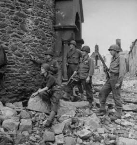 """David E. Sherman: """"Lee Miller con soldados americanos. Alemania, 1944"""" - La imagen muestra parte de una estructura en ruinas. Sobre los escombros, en primer término, aparece sentada Miller vestida con traje de campaña y casco. Detrás de ella, en pie, tres soldados norteamericanos armados vigilan mirando en la misma direcciín que ella. Pulse para ampliar."""
