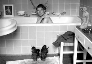 """David E. Sherman: """"Lee Miller en la bañera de Hitler"""" (1945) - La imagen muestra un cuarto de baño limpio y grande. En primer término se aprecia a la derecha una consola son cajones sobre la que hay una escultura de una mujer desnuda agachada. A continuación hay un taburete sobre el que descansa un uniforme y, a su lado, una botas. A la izquierda aparece parte de un lavabo. Y al fondo, ocupando todo el ancho de baño, una gran bañera, con el frente alicatado, en la que se ve a Miller tomando un baño y pasándose una esponja por el hombro mientras mira a la cámara. Sobre la repisa del fondo aparecen varios soportes para poner jabón y una foto enmarcada de Adolf Hitler. Pulse para ampliar."""