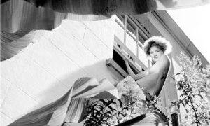 Roland Penrose - Fotografía de Lee Miller en Lamb Creek, Cornualles (1937) - La imagen muestra un plano contrapicado (tomado desde abajo) de Lee en lo alto de una escalera de madera en el lateral de una casa. Va desnuda de cintura para arriba y lleva una larga falda formada por una tela de flores que cae en pliegues alrededor de sus piernas. Pulse para ampliar.
