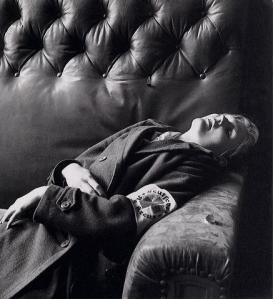 """Lee Miller - """"Hija de un oficial alemán suicidada con cianuro. Leipzig, 1945"""". La imagen muestra a una muchacha rubia muy joven, que lleva un abrigo de oficial alemán que le queda grande. Está tirada sobre un sillón, muerta, con la boca entreabierta y los brazos aferrados al abrigo como si tuviera frio. Pulse para ampliar."""