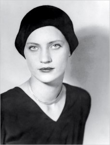 Man Ray - Retrato de Lee Miller (1930) - La imagen muestra un primer plano largo, cortado un poco más abajo de los hombros, de Lee con el rostro de frente y el cuerpoi ligeramente en tres cuartos. Lleva un jersey negro con cuello de pico y un sombrero negro en forma de casquete le cubre la cabeza. Mira fijamente a la cámara. Pulse para ampliar.