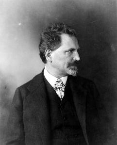 Retrato de A. M. Mucha (1906) - La imagen muestra una fotografía en blanco y negro con el retrato en plano medio del artista. Está vestido con un traje negro, camisa blanca y corbata. Tiene bigote y perilla cana y gira su rostro hacia la izquierda, de modo que le vemos de perfil. pulse para ampliar.