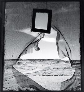 Lee Miller - Retrato del espacio (1937) - La imagen está tomada desde el interior de una tienda de campaña desde la que se ve una mosquitera rota en su centro, un espejo con marco de madera colgado del techo y afuera, la inmensa extensión del desierto. Pulse para ampliar.