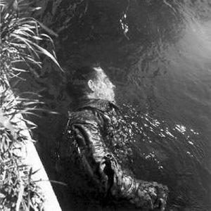"""Lee Miller - """"Guardián de Dachau muerto en el agua"""" (1945) - La imagen muestra un plano picado (desde arriba) de un guardián del campo de concentración de Dachau semisumergido en una especie de acequia. Va vestido aún con el uniforme y parte de su cuerpo se sumerge en el agua. En el borde de la acequia asoman unas cuantas hierbas que enmarcan la figura por la izquierda. Pulse para ampliar."""